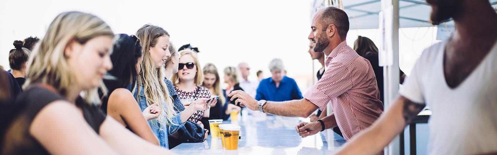 Mennesker i en bar sød bartender der servere øl